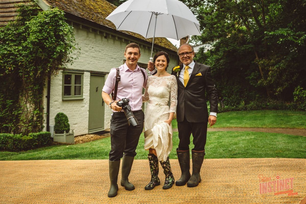 wedding photographer, bride and father of the bride ready to walk to the church. What to do if it rains on my wedding day?