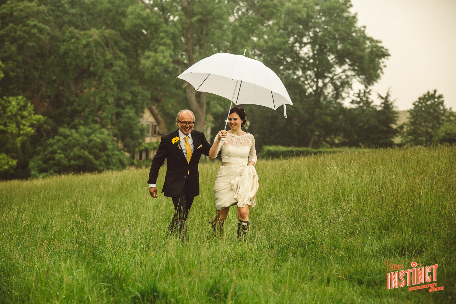 Father and his daughter on a rainy wedding day walking across a field