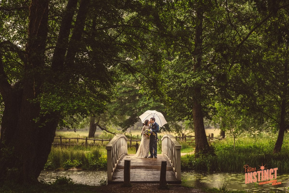 Beautiful image of the bride and groom on a Victorian bridge in the pouring rain. What to do if it rains on my wedding day?