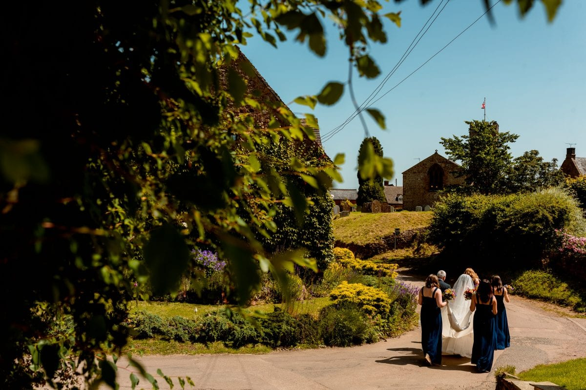 Bridesmaids escort the bride through the village of Epwell in Oxfordshire