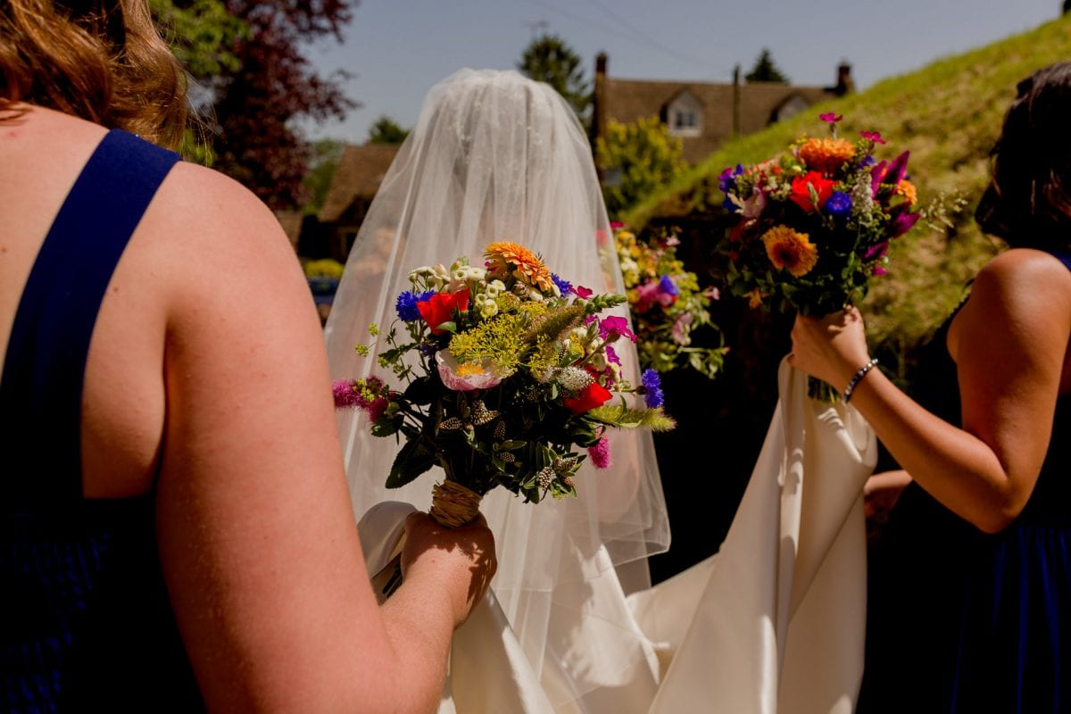 Vibrant bridal flowers held by the bridesmaid at a wedding in Epwell Oxfordshire