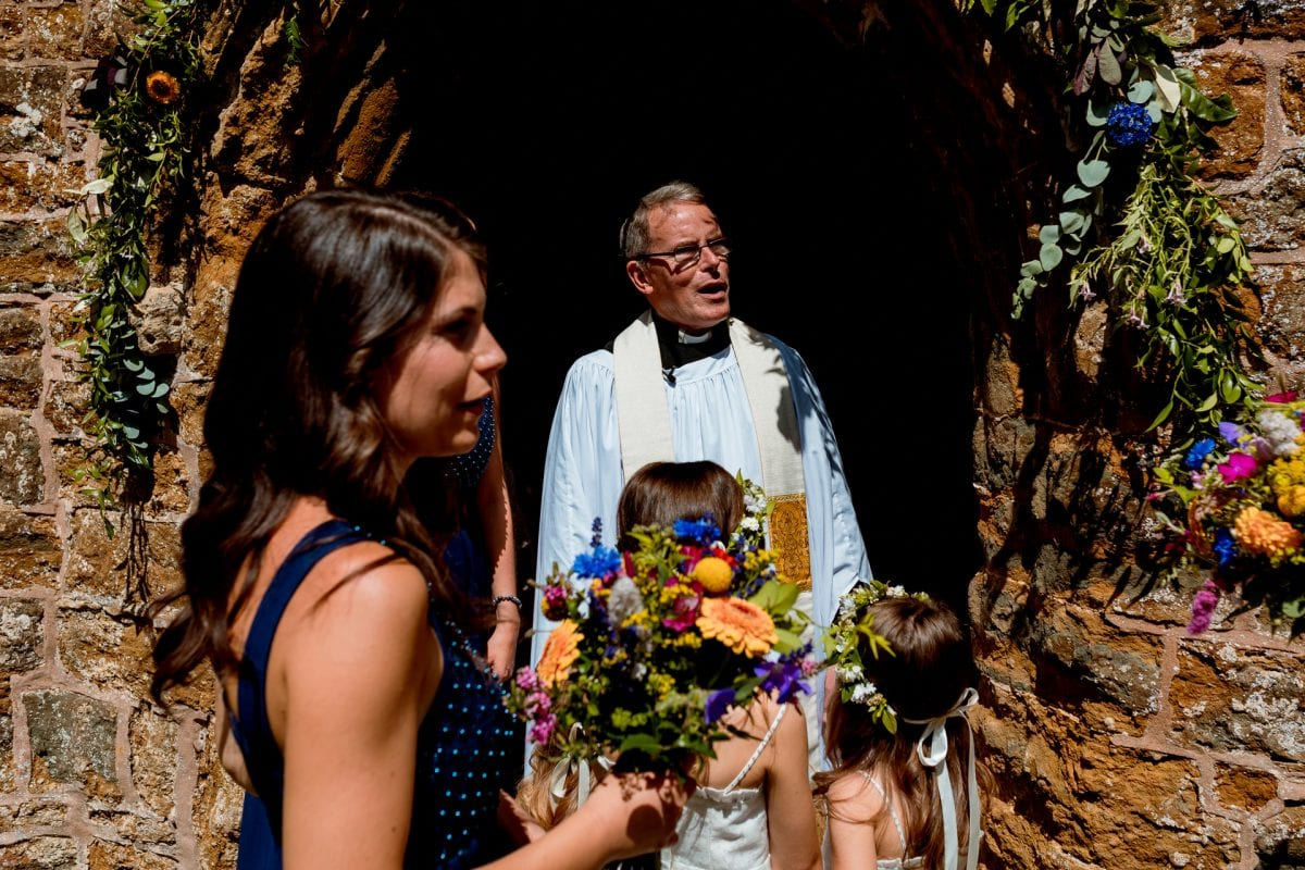 The bride being greeted by the vicar of St Anne's church in Epwell Oxfordshire