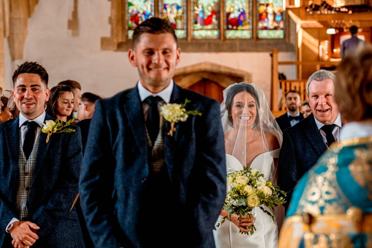 St Mary's Church Kidlington bride being walked down the aisle by her father to an excited groom