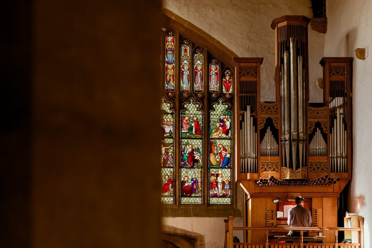 St Mary's Church Kidlington organ and organist playing in front of a large stain glass window