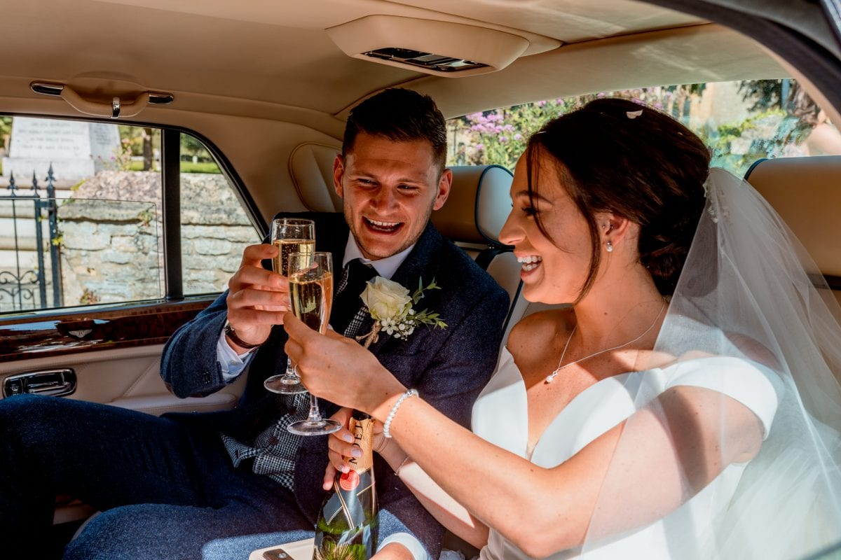 St Mary's Church Kidlington bride and groom sharing champagne in the wedding car