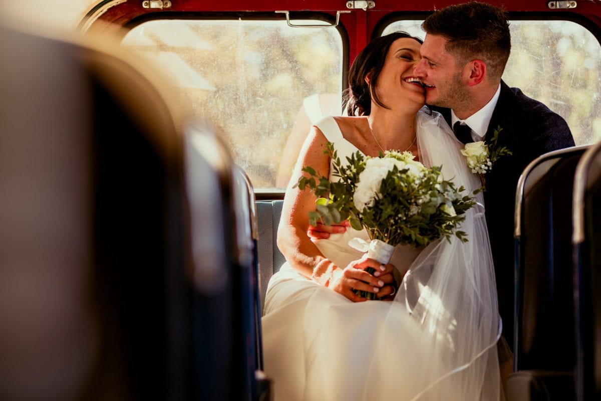 Wedding couple on the back seat of a vintage bus on their wedding day laughing