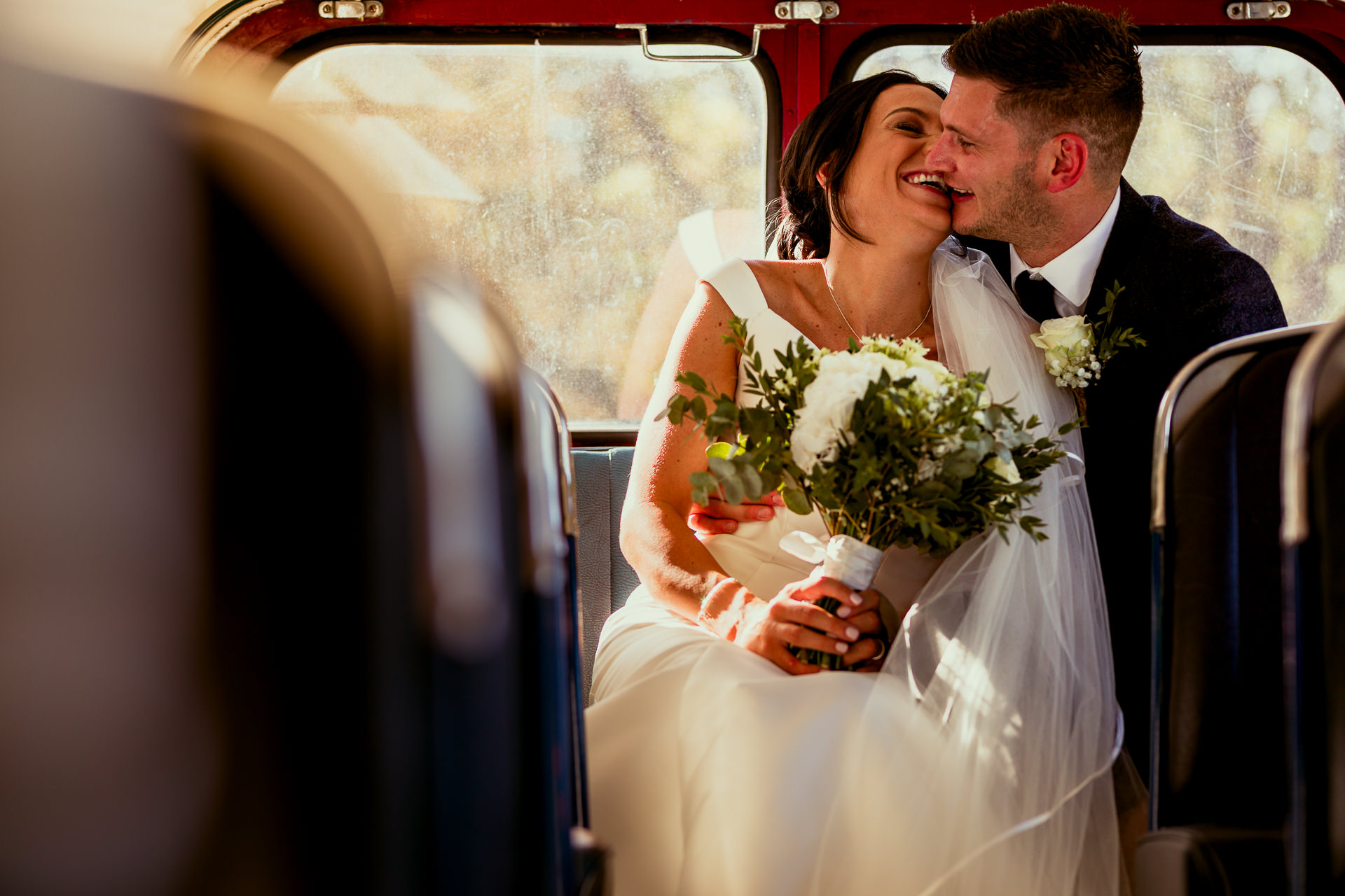 Wedding couple on the back seat of a vintage bus at Lains Barn in Oxfordshire on their wedding day laughing