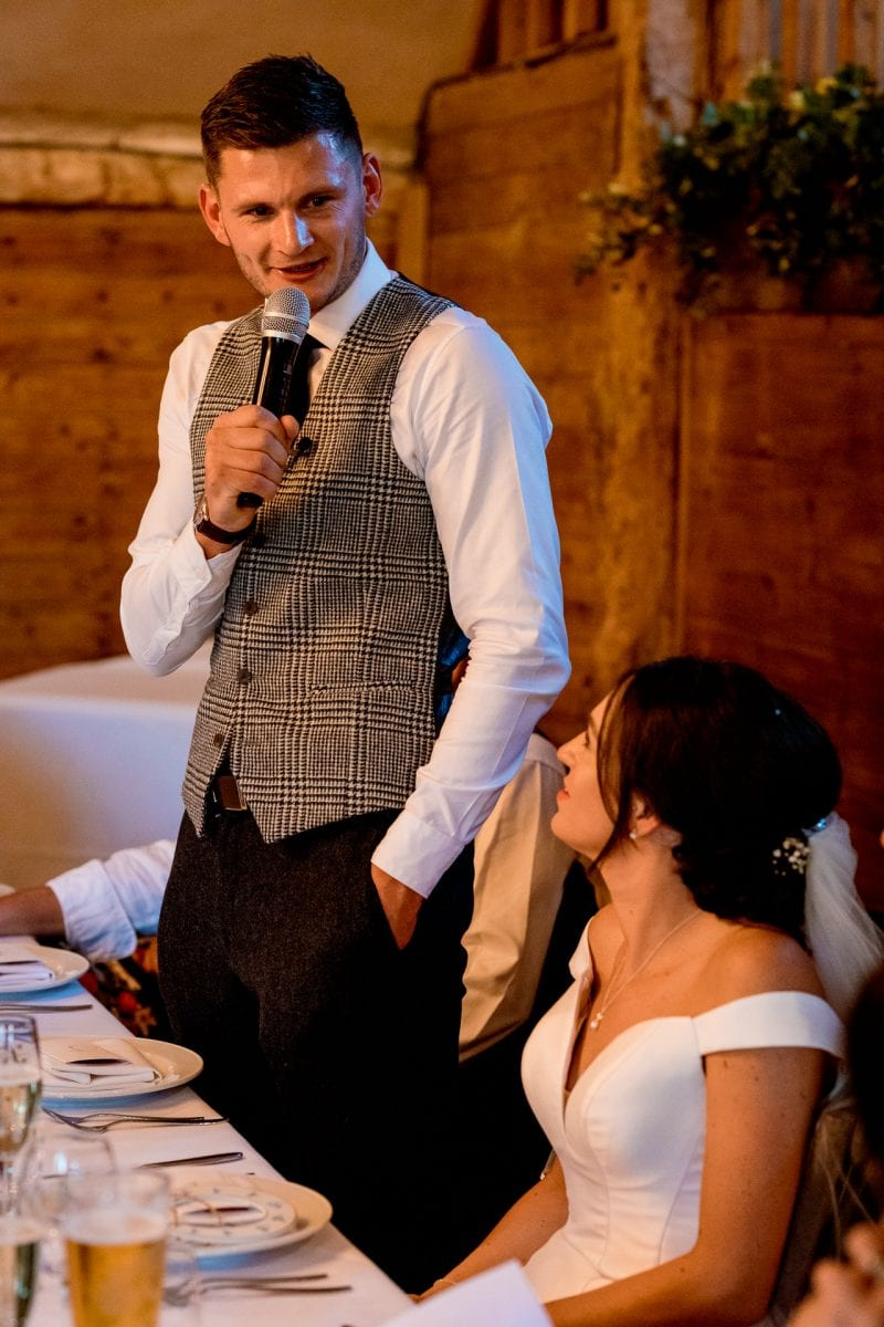 lains barn wedding photography blog oxfordshire groom talking to his bride during the speeches