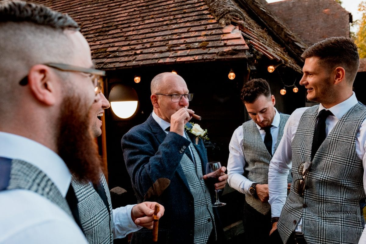 lains barn wedding photography blog oxfordshire grooms party having cigars