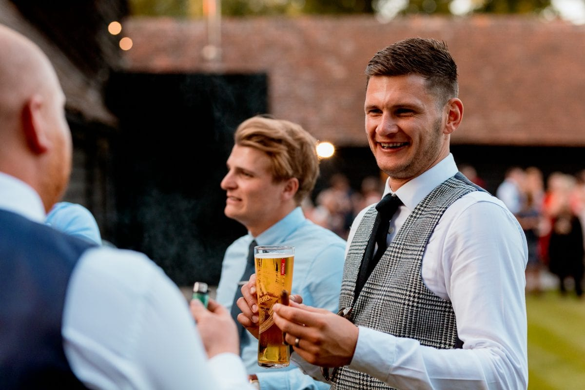 lains barn wedding photography blog oxfordshire groom relaxing with cigar and beer