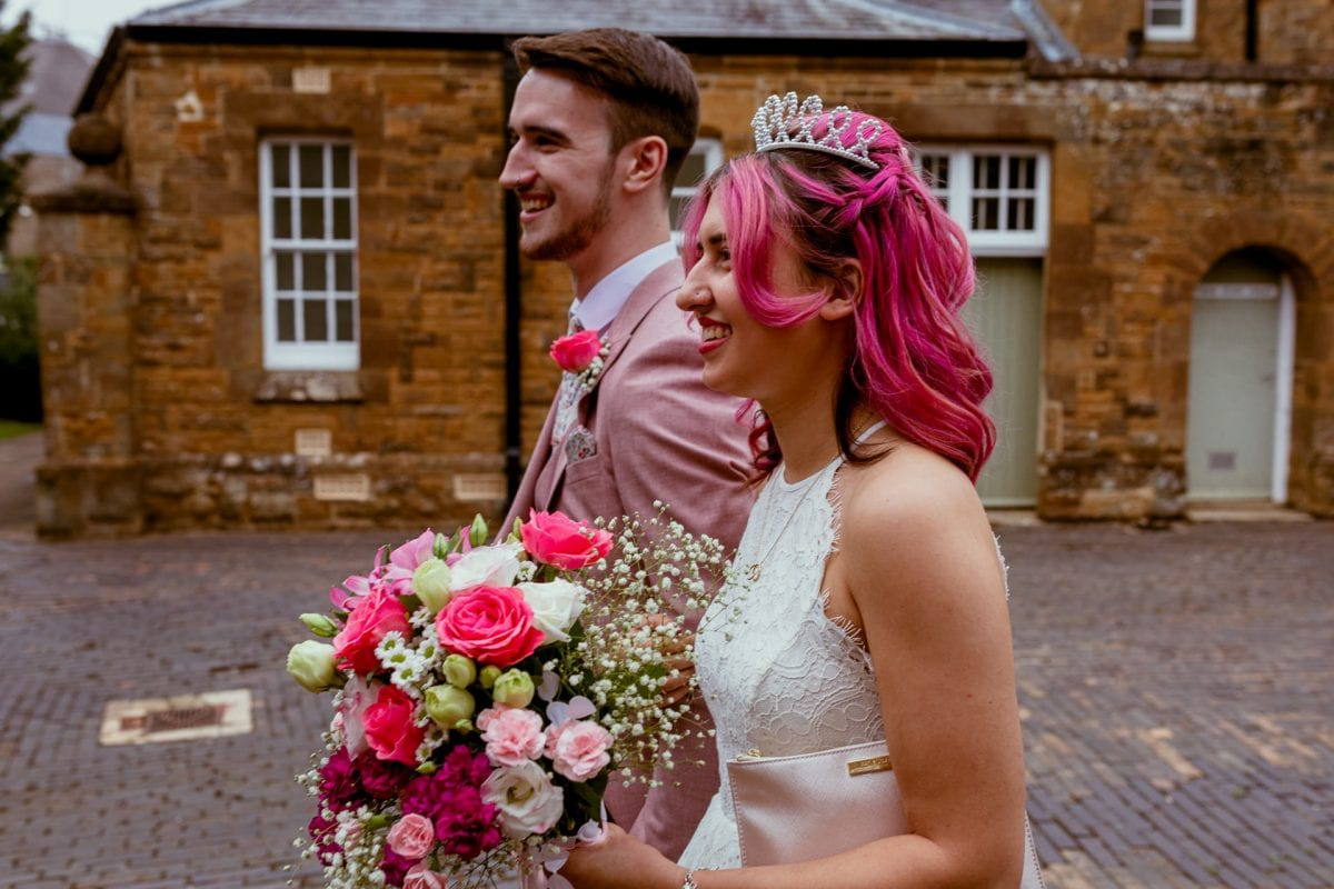 bride and groom walking together with pink hair and a pink suit