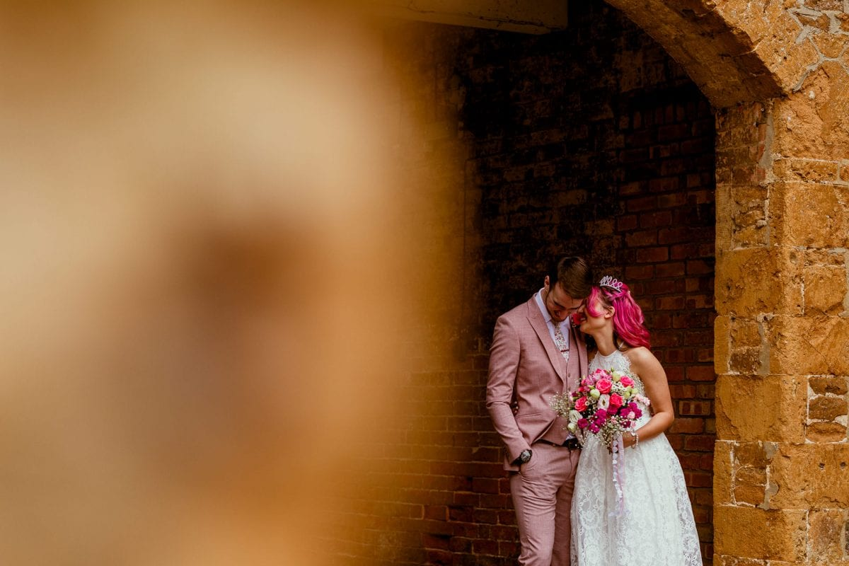 Bride whispering into her grooms ear