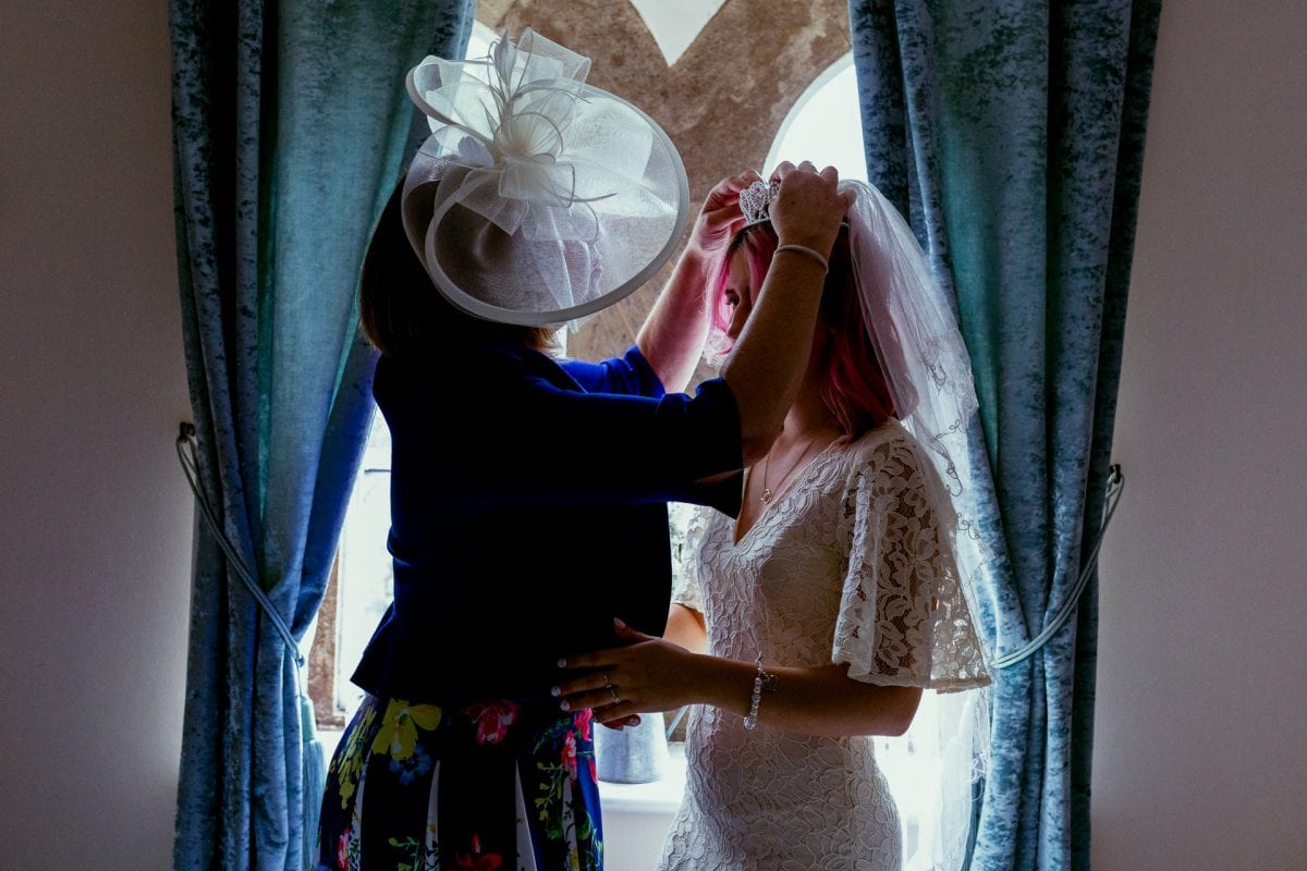 Mother of the bride putting on her daughters veil