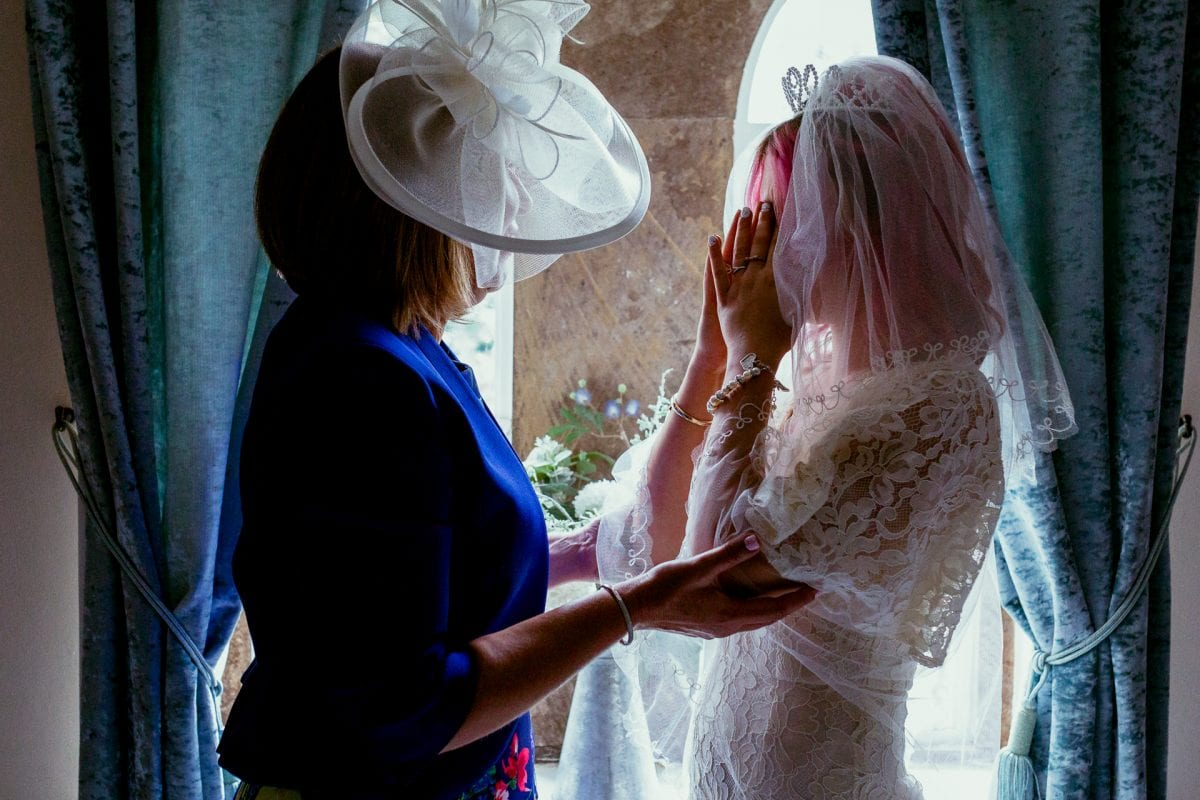 Mother of the bride holding her tearful daughter