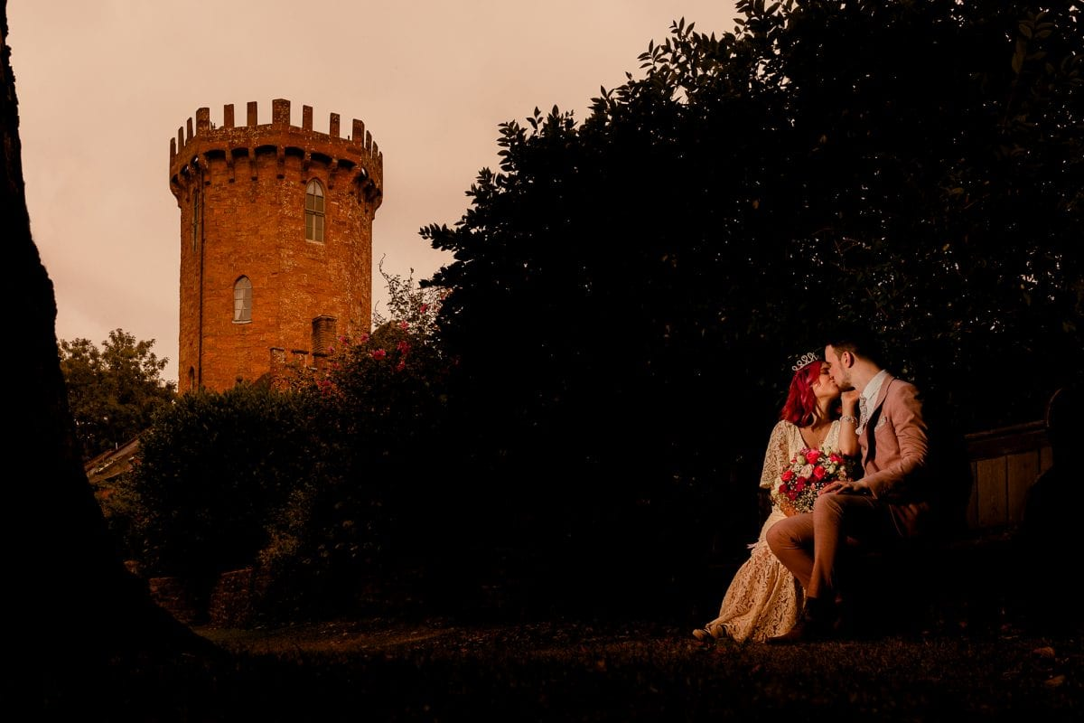 Bride and Groom kissing on a bench at The Castle Edgehill Oxfordshire