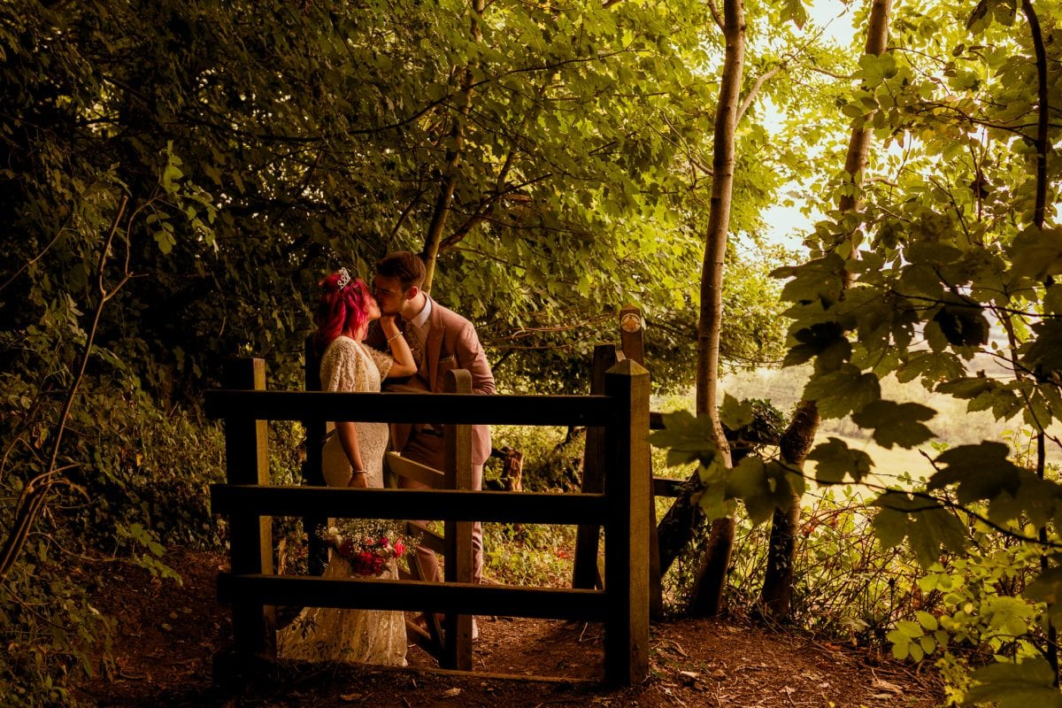 A kissing gate with a kissing wedding couple
