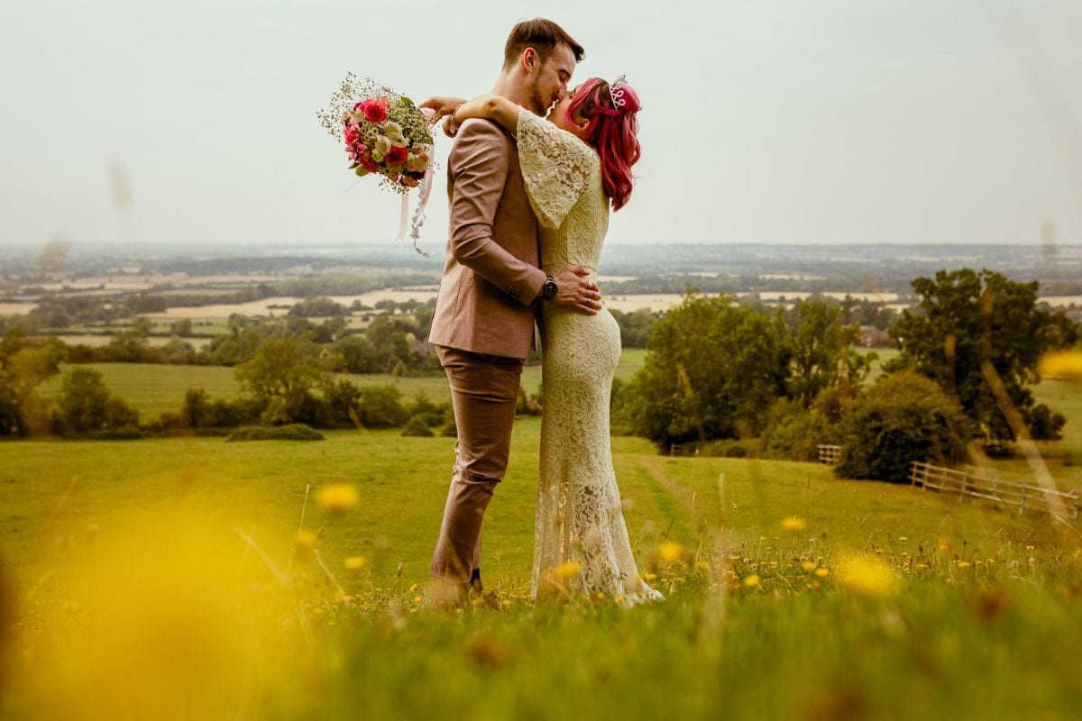 couple kissing on a hill surrounded my yellow flowers