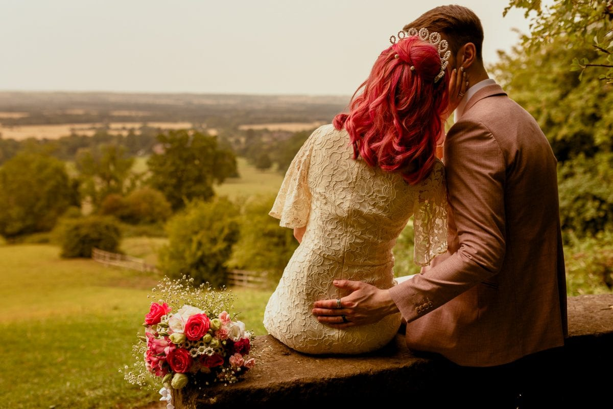 wedding couple sat on a bench overlooking a beautiful view