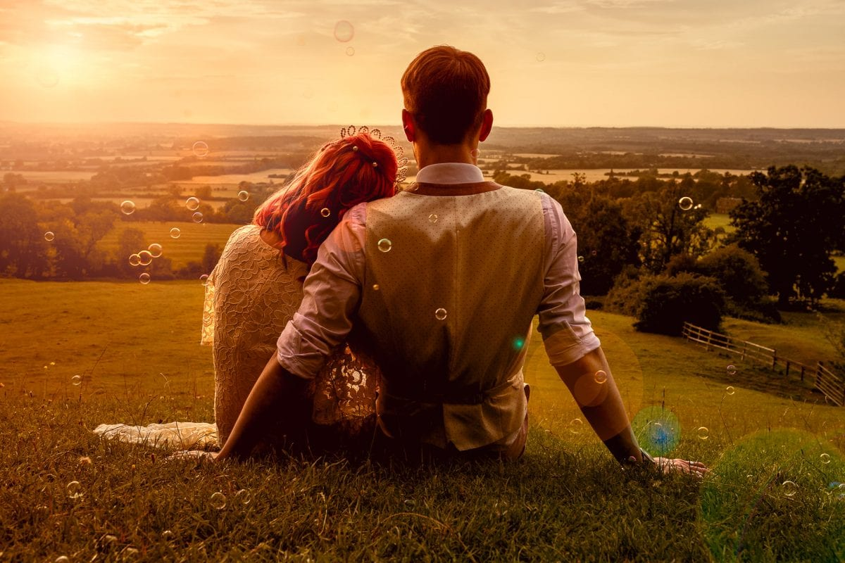 Wedding couple sat on a hill looking at the sunset near edgehill castle, with bubbles floating around them